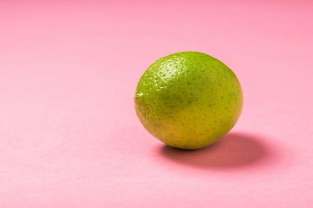 Citron vert mûr sur fond rose vif. agrumes pour faire une boisson.