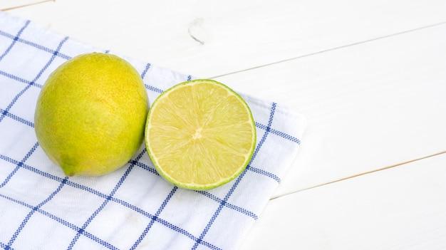 Citron vert sur une table en bois blanche.