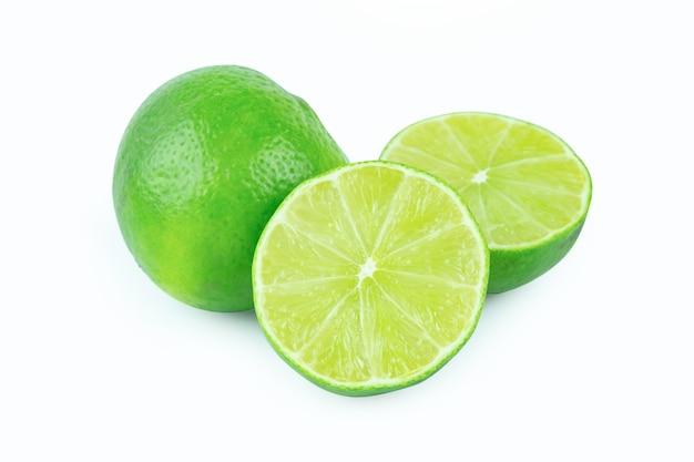 Citron vert avec des tranches à moitié isolé sur fond blanc. agrumes verts. avec chemin de détourage