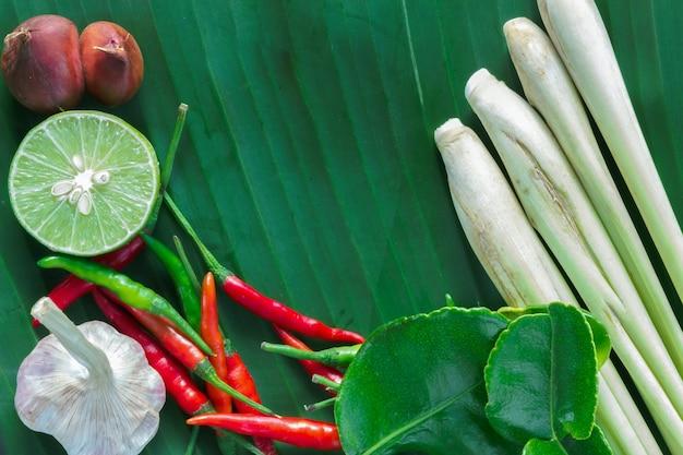 Citronnelle, piment rouge et feuilles de lime kaffir sur fond de feuille de bananier.