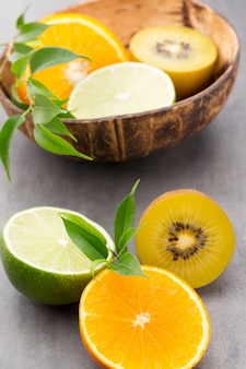 Citrons d'agrumes mixtes, orange, kiwi, limes sur fond gris.