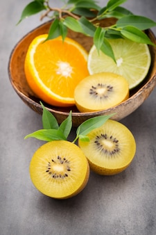 Citrons d'agrumes mixtes, orange, kiwi, limes sur fond gris