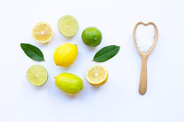 Citrons et citrons verts mûrs avec du sel sur blanc