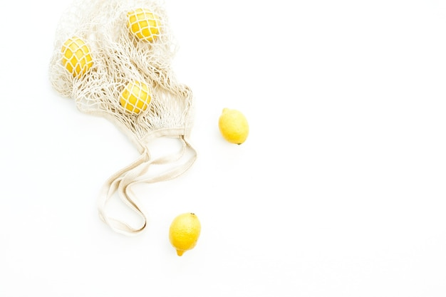 Citrons crus frais dans un sac à cordes. mise à plat, concept d'agrumes vue de dessus