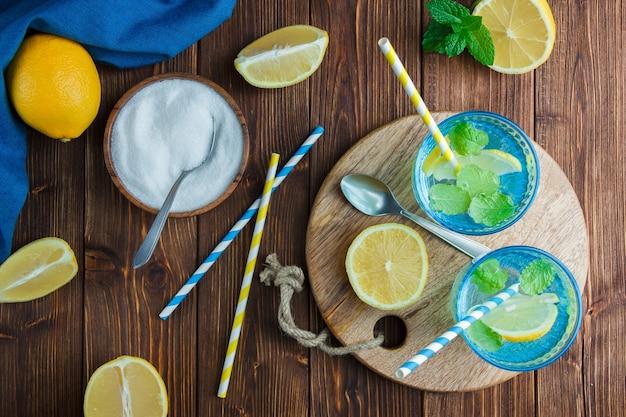 Citrons dans un bol avec un chiffon bleu, couteau en bois et bouteille de jus, pailles, bol de sel vue de dessus sur une surface en bois