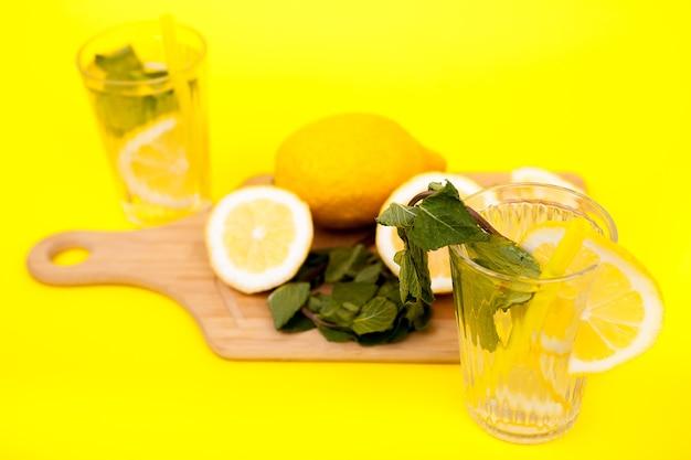 Citrons et eau détox faite d'eux sur fond jaune