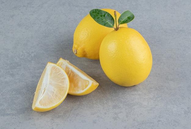 Citrons entiers et tranchés affichés sur marbre