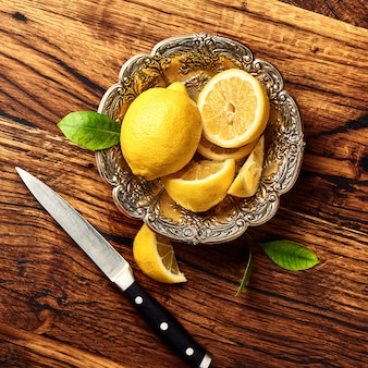 Citrons avec feuilles sur table en bois de chêne. vue de dessus des fruits avec couteau.