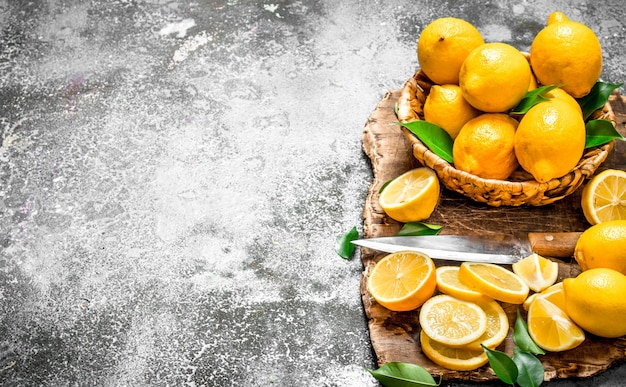 Citrons frais dans un panier avec un couteau sur une planche à découper.