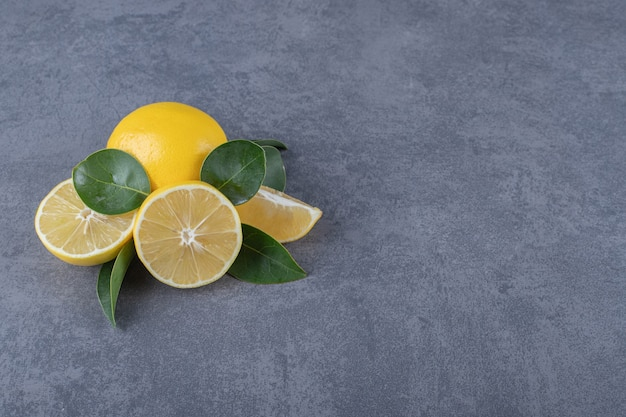 Citrons frais entiers ou coupés à moitié sur fond gris.