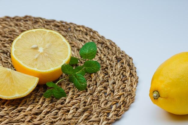 Citrons frais avec des feuilles sur tapis blanc et en osier