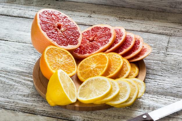 Citrons frais en tranches, pamplemousses, oranges sur une planche à découper en bois avec un couteau