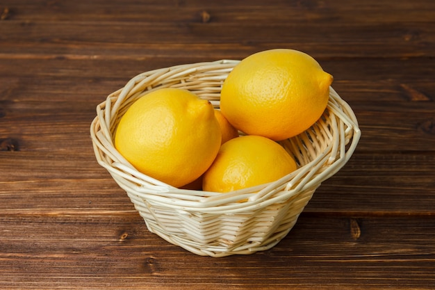 Citrons jaunes dans un panier sur une surface en bois. vue grand angle.