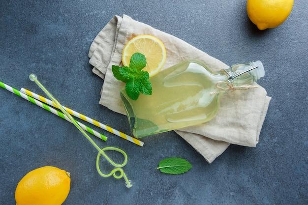 Citrons jaunes avec du jus de citron sur un tissu blanc et des pailles à plat sur une surface blanche