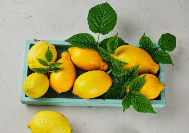 Citrons jaunes entiers mûrs sur une planche de bois bleue