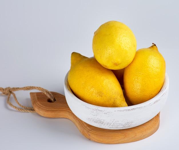 Citrons jaunes entiers mûrs sur une planche de bois