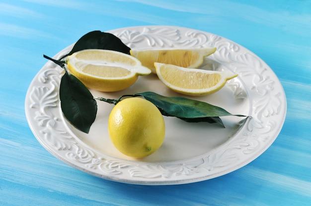 Citrons jaunes frais avec des feuilles sur une assiette sur fond bleu
