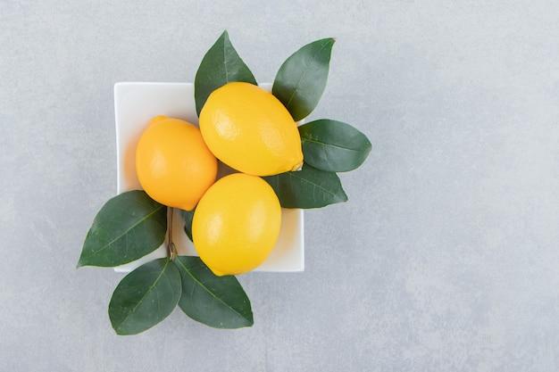 Citrons jaunes frais sur plaque blanche.