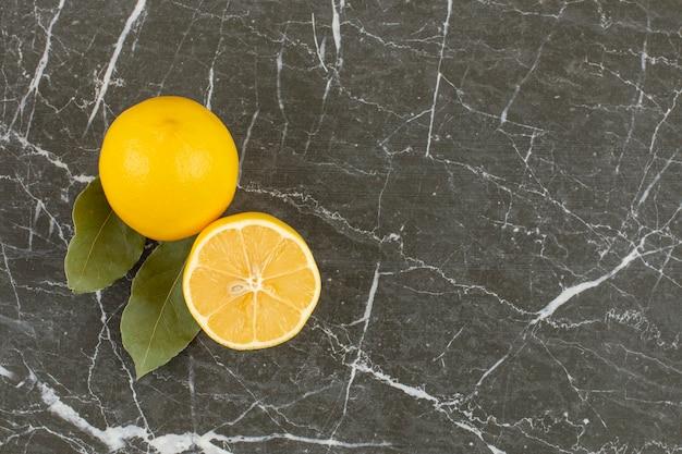 Citrons de jus de fruits frais sur gris.
