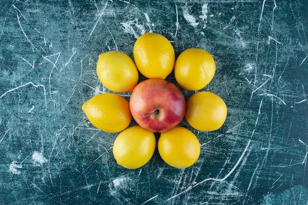 Citrons juteux et pomme rouge sur table en marbre.