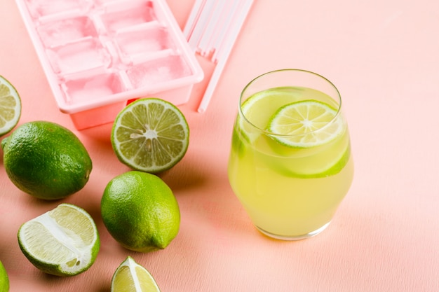 Citrons avec limonade, bac à glaçons, pailles high angle view on a pink