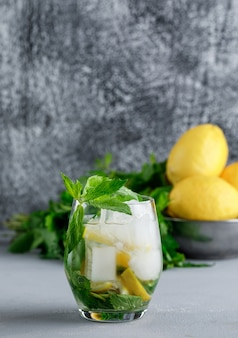 Citrons et menthe dans un bol avec vue côté eau détox glacée sur grunge et surface grise