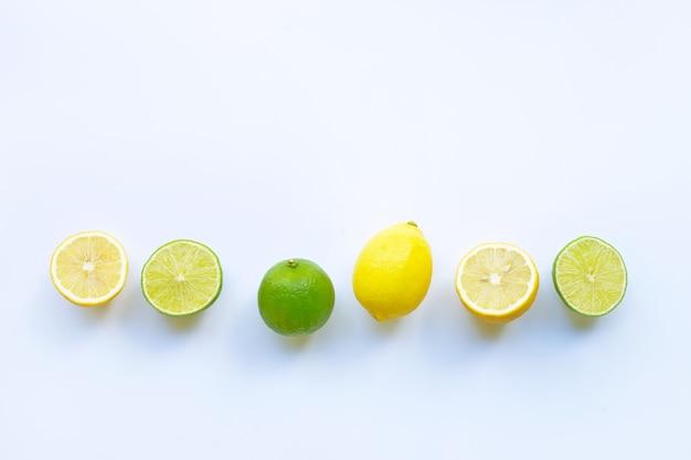 Citrons mûrs et citrons verts sur blanc.