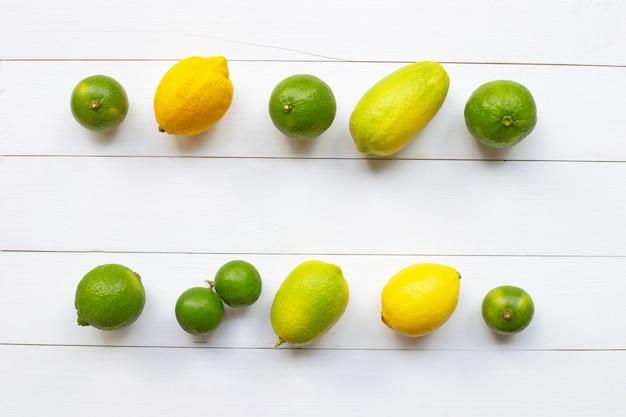 Citrons mûrs et citrons verts sur bois blanc.