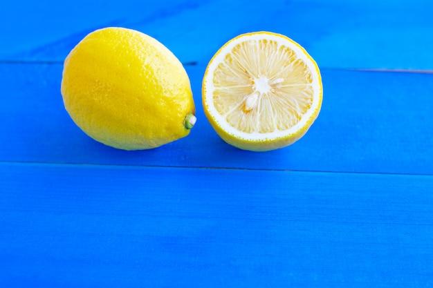 Citrons mûrs et citrons verts sur bois bleu