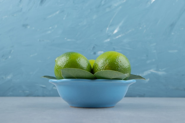 Citrons mûrs frais dans un bol bleu.