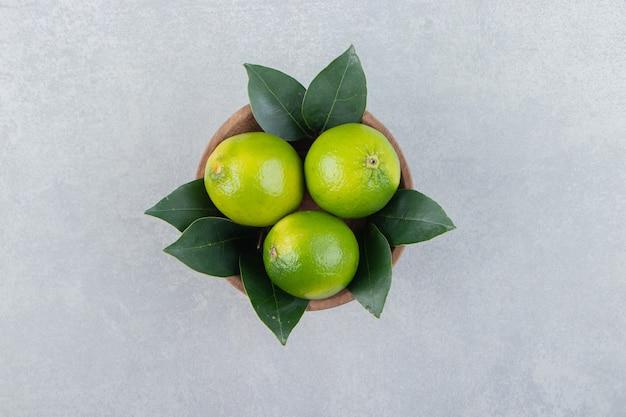 Citrons mûrs frais dans un bol en bois