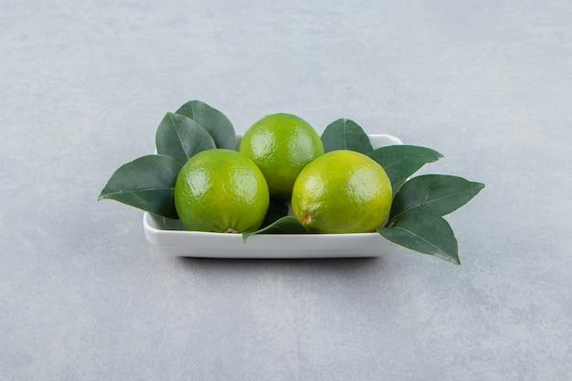 Citrons mûrs frais sur plaque blanche
