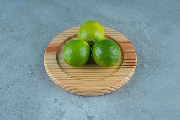 Citrons non mûrs sur une plaque en bois , sur le fond de marbre. photo de haute qualité