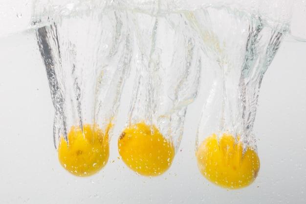 Citrons tombant profondément dans l'eau