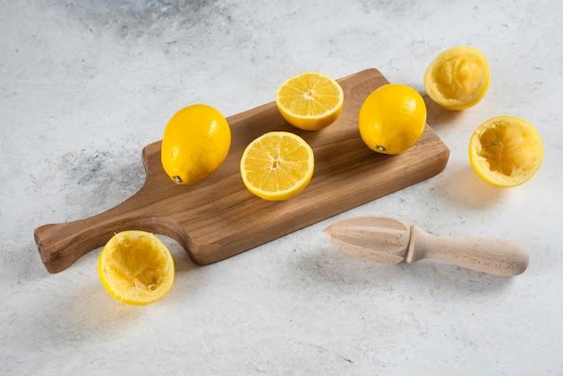 Citrons tranchés et entiers avec alésoir en bois.