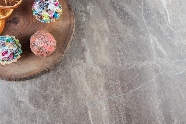 Citrons tranchés et mini gâteaux sur une planche en marbre.