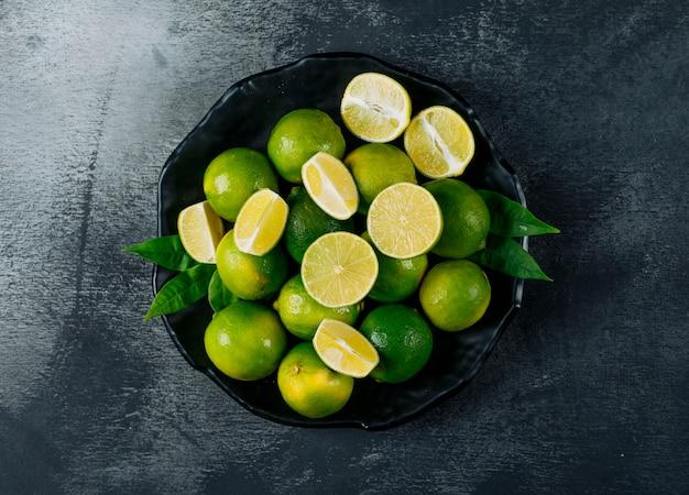 Citrons verts dans une assiette avec des tranches vue de dessus sur un fond texturé noir