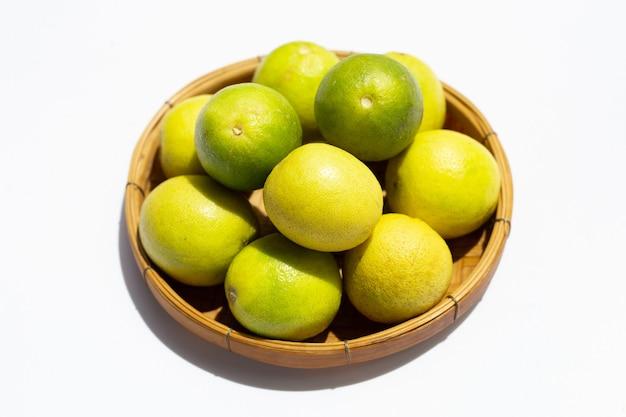 Citrons verts dans un panier en bambou sur blanc