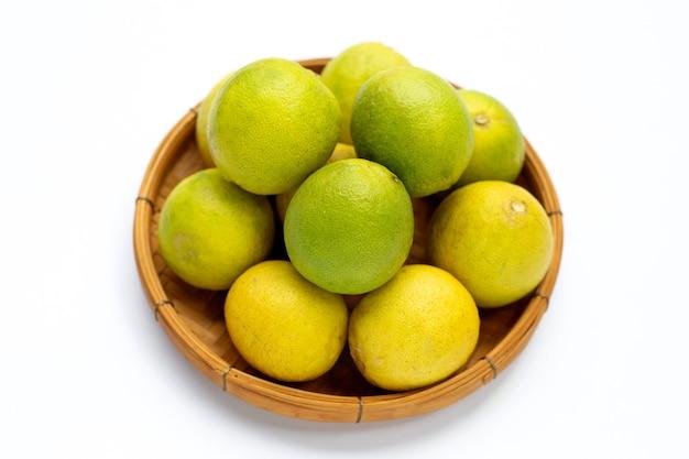 Citrons verts dans un panier en bambou sur fond blanc.