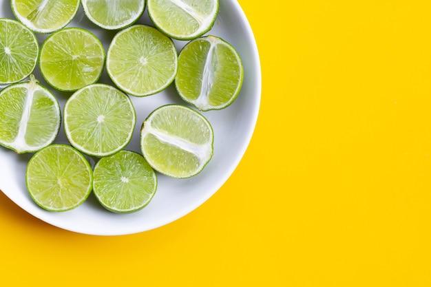 Citrons verts frais dans un plat blanc sur fond jaune. vue de dessus