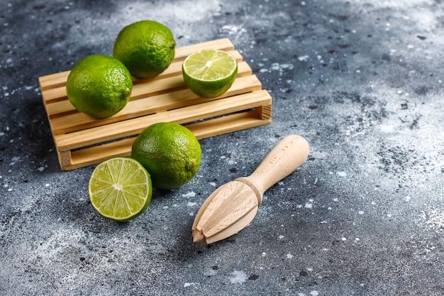Citrons verts frais avec du jus d'agrumes en bois