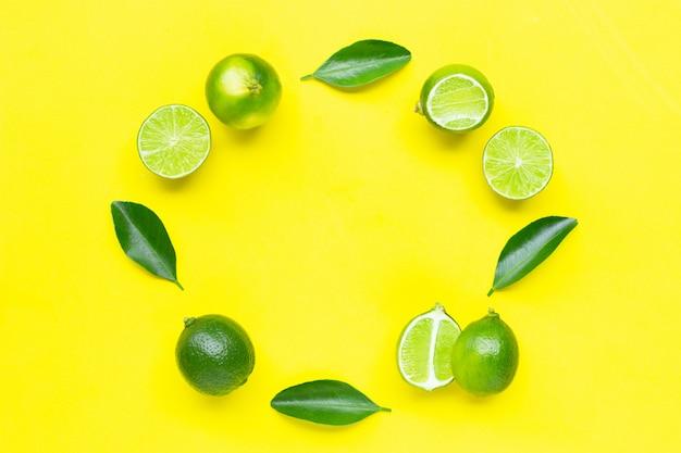 Citrons verts frais avec des feuilles sur fond jaune.