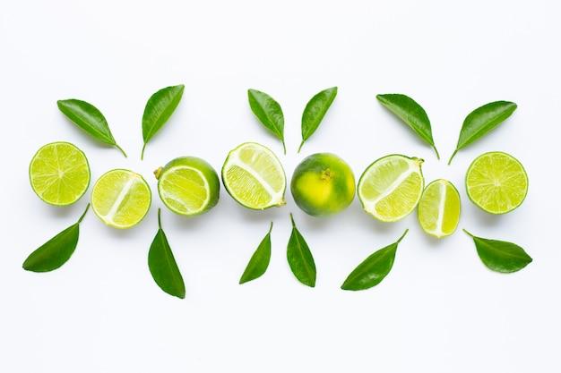 Citrons verts frais avec des feuilles isolées sur blanc