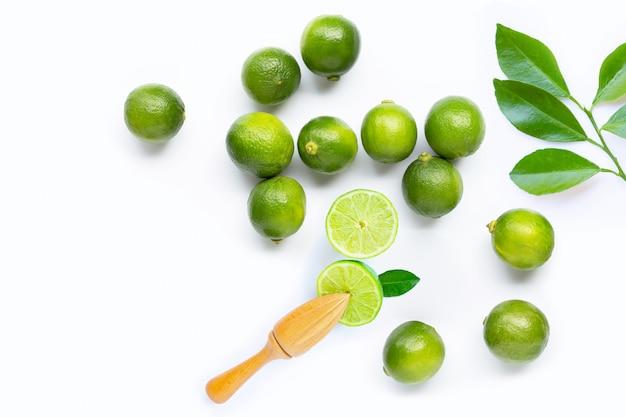 Citrons verts frais et feuilles avec presse-agrumes en bois blanc.
