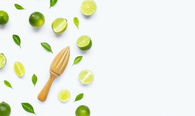 Citrons verts frais et feuilles avec presse-agrumes en bois sur fond blanc.