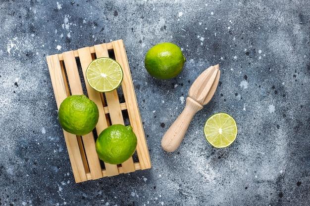Citrons verts frais avec presse-agrumes en bois, vue de dessus