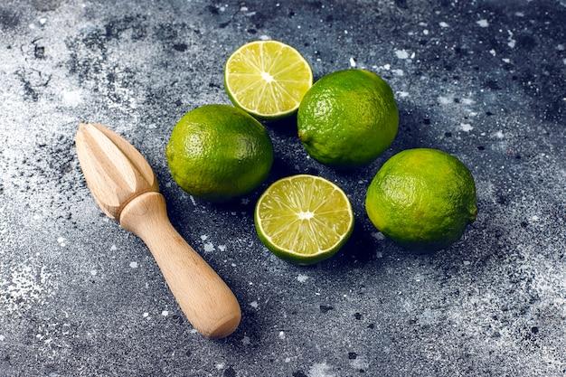 Citrons verts frais avec presse-agrumes en bois, vue du dessus