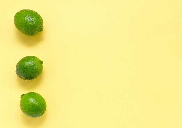 Citrons verts juteux frais sur un fond uniforme jaune
