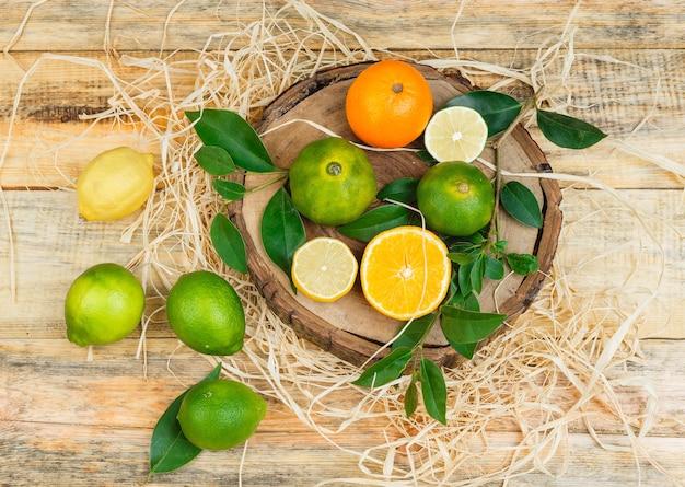 Citrons verts, oranges et mandarines dans une assiette en bois