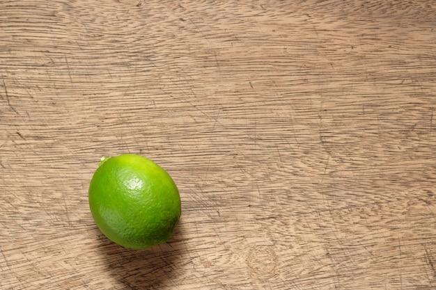 Citrons verts posés sur un plancher en bois